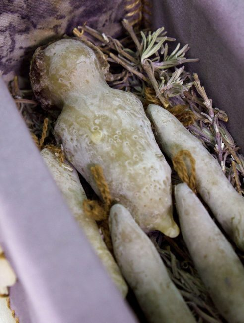 """Funerary Doll"" (detail). Clay from my parents' backyard, beeswax, garden flowers, sumac cones, walnut leaves, found box, wool, cotton and beach glass. 5""x8""x3½"". 2019."